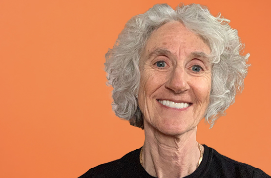 Photo of a woman with short white hair, blue eyes, and a black shirt smiling at the camera over an orange background