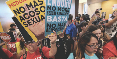 a group of people in a room holding signs in Spanish calling for and end to sexual harassment