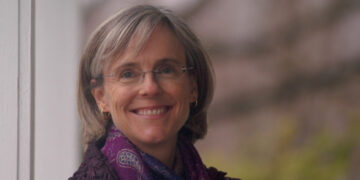 Photo of WDN member Sage Wheeler, a white women wearing glasses and a purple scarf. She has shoulder-length grey hair and smiles at the camera.