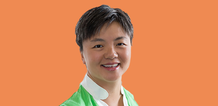Photo of Sharon Chen, an asian woman with short grey hair smiling at the camera. She is wearing a green shirt with a white collar. The background of the photo is orange.