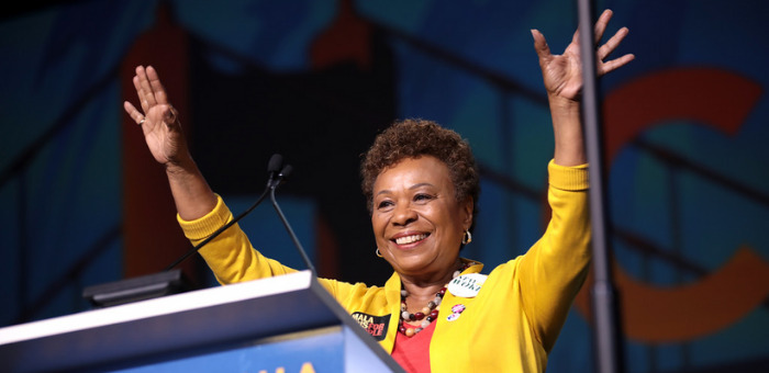 Photo of Representative Barbara Lee, a Black woman with short textured hair, standing on a podium and smiling and waving. She is wearing a yellow jacket and orange shirt