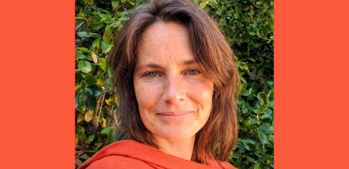 A photo of WDN member Amanda Coslor, she has short brown hair, blue eyes, and is smiling slightly at the camera. She wears an orange sweater and is outside in front of a bush.