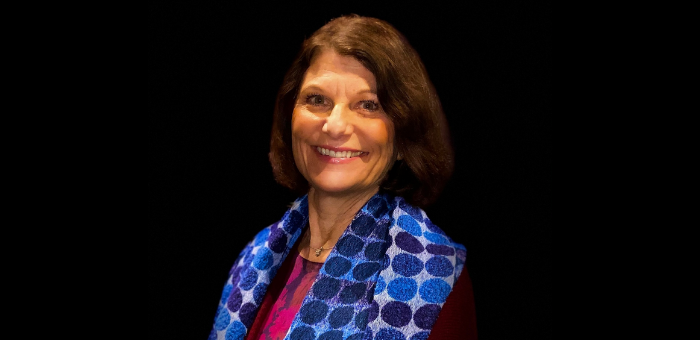 Cheryl Houser stands in front of a black background and smiles at the camera. She has shoulder length brown hair and wears a pink blouse and blue scarf.