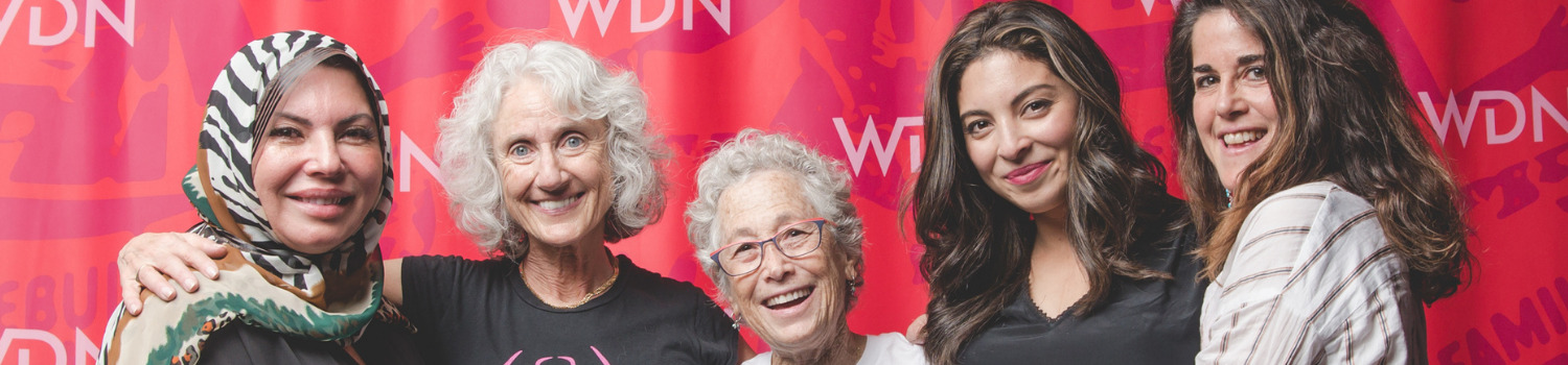 photo of 5 WDN members in front of a background with the WDN logo, smiling at the camera