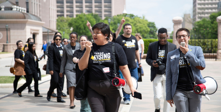 A group of protesters walk wearing Texas Freedom Network Education Fund shirts. The two people at the front speak into bullhorns