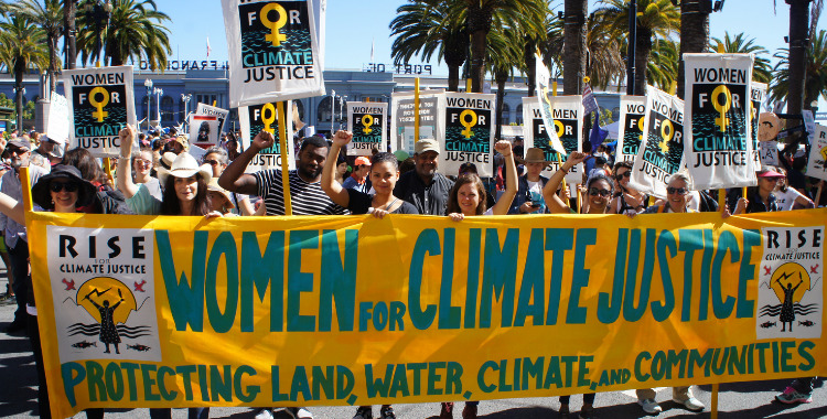 A group of people hold signs and a banner that reads Women for Climate Justice