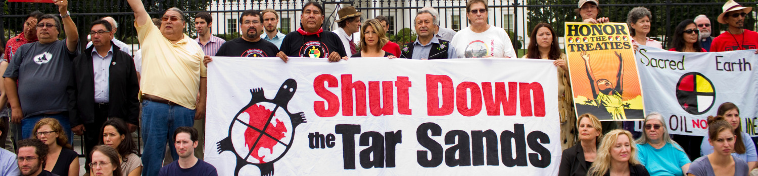 A crowd of people stand in front of a government building holding signs that say shut down the tar sands and end Keystone XL