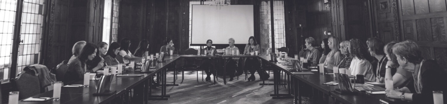 A group of women sit at a u-shaped table with paperwork in front of them. Image is in black and white.