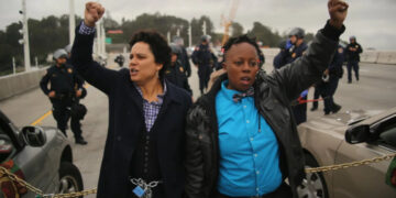 A photo from the San Francisco Chronicle showing Kathryn Snyder, left and Nolizwe Nondabula, right, raising their fists as they block traffic during a demonstration against police brutality. The photo was taken on the eastern span of the San Francisco-Oakland Bay Bridge in Oakland, California on January 18, 2016.