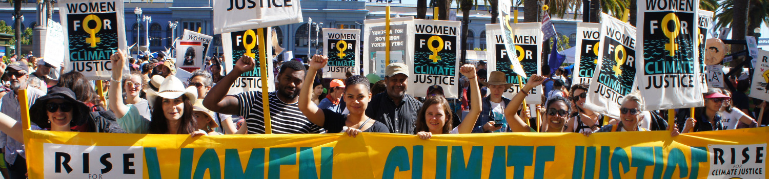 """Protest rally with a group of people holding up individual and banner signs saying """"women for climate justice"""""""