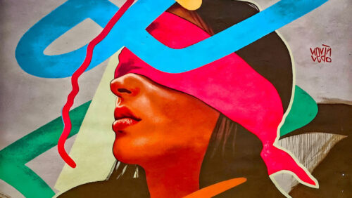 Photo of a colorful mural. The mural depicts a person with long hair with a bright pink blindfold tied over her eyes. Colorful lines and loops are drawn in the background, some cover part of the person's face