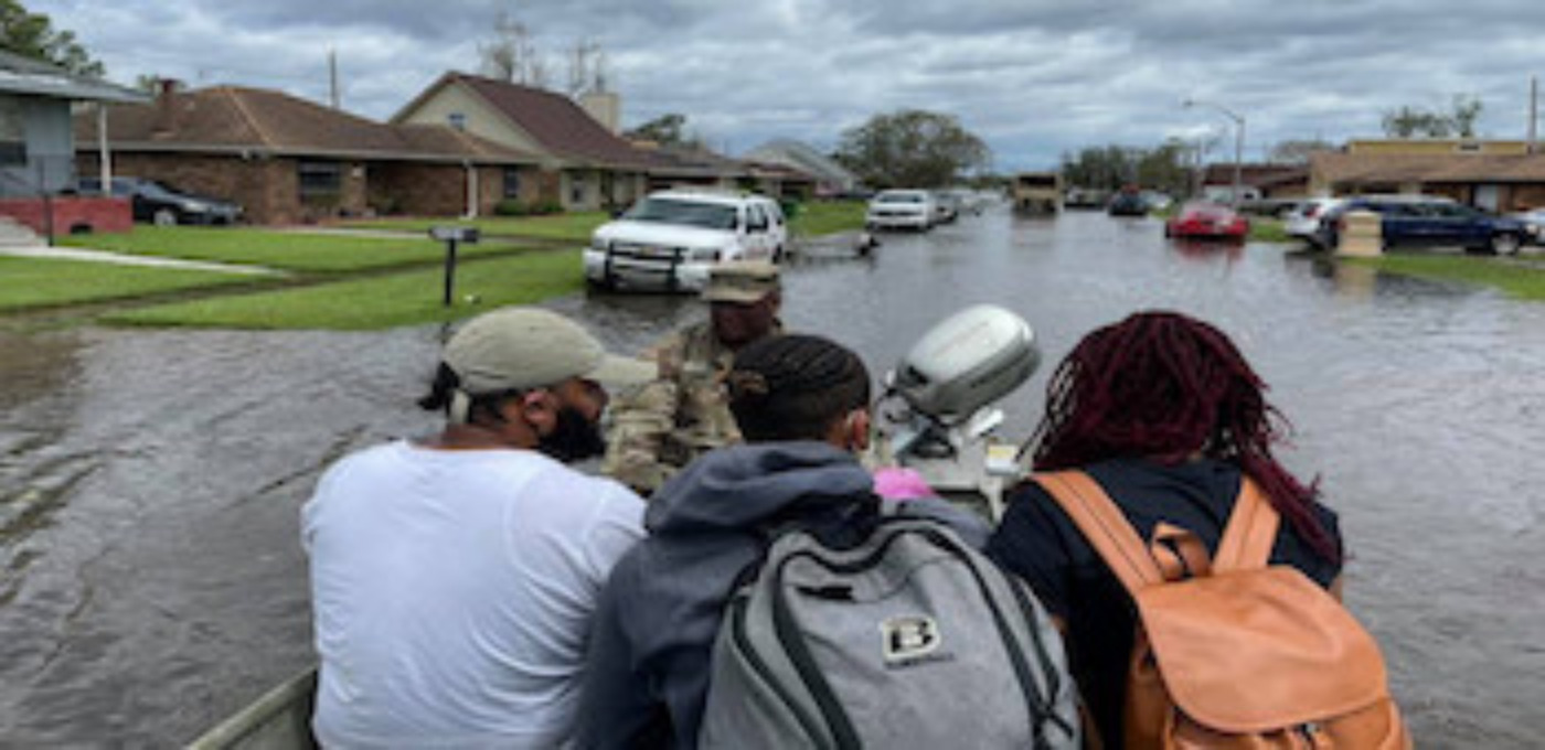 Photo of four people riding in a boat down a flooded residential street
