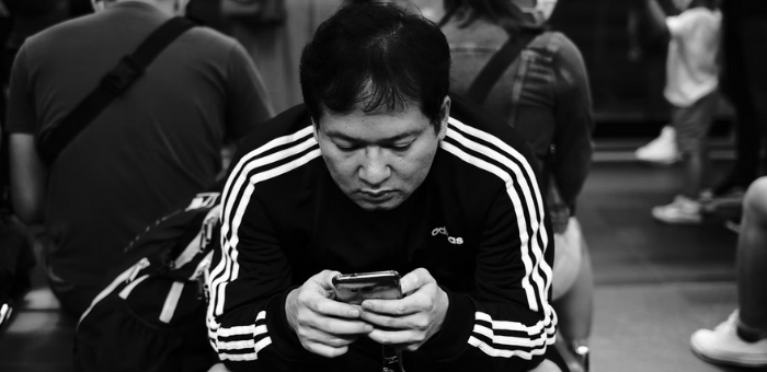 A black and white image of a person sitting on a bench in a crowded public area staring at their mobile pone screen