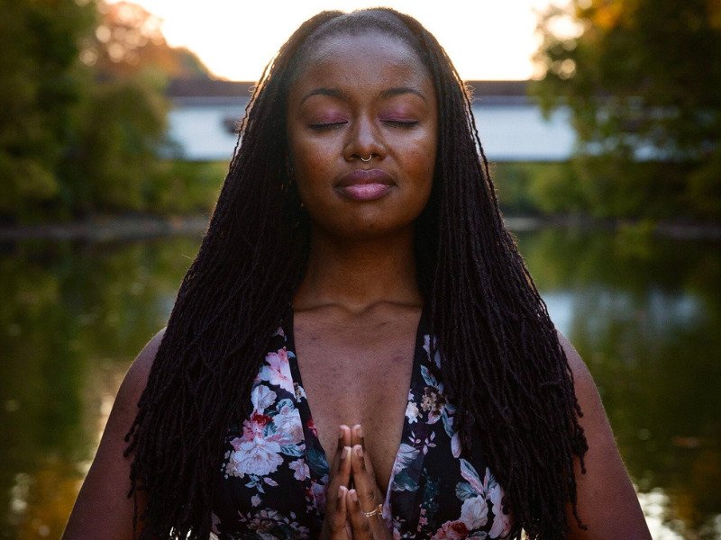 Photo of Charlie Redd, a person with brown skin and long hair in locks. They stand in front of a lake with their eyes closed, their hands pressed together in front of them in namaste