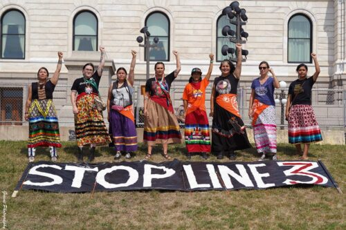 """A line of people in traditional dress stand with fists raised. A banner lays on the ground in front of them that reads, """"STOP LINE 3"""""""